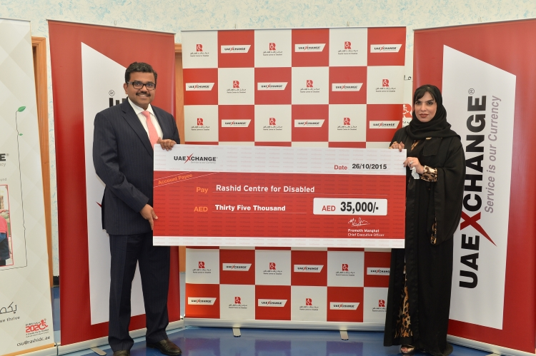 Mr. Promoth Manghat, CEO, UAE Exchange, handing over the cheque to Mrs. Maryam Othman, General Manager, Rashid Centre